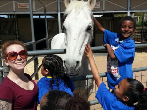 teacher with her students taking a photo with a horse